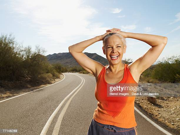 Senior Hispanic woman taking break from jogging