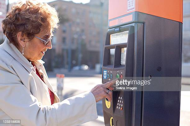 senior hispanic woman using parking meter - parking meter stock photos and pictures