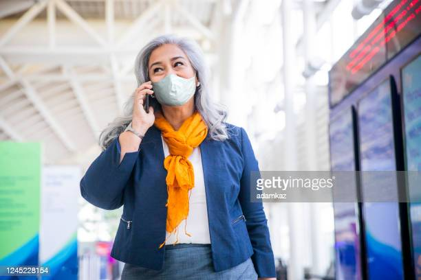 senior hispanic woman using wearing a mask smartphone in the airport - adamkaz stock pictures, royalty-free photos & images