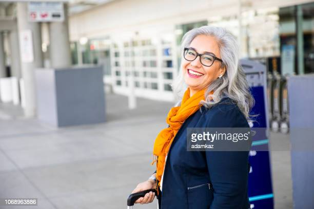 senior hispanic woman waiting outside the airport - mexican business women stock photos and pictures