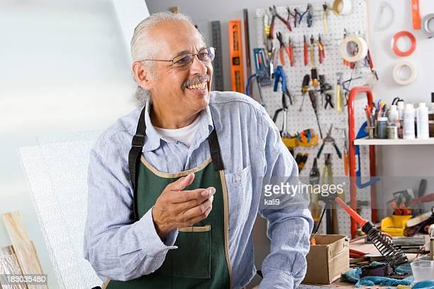 Senior Hispanic worker with tools in repair shop