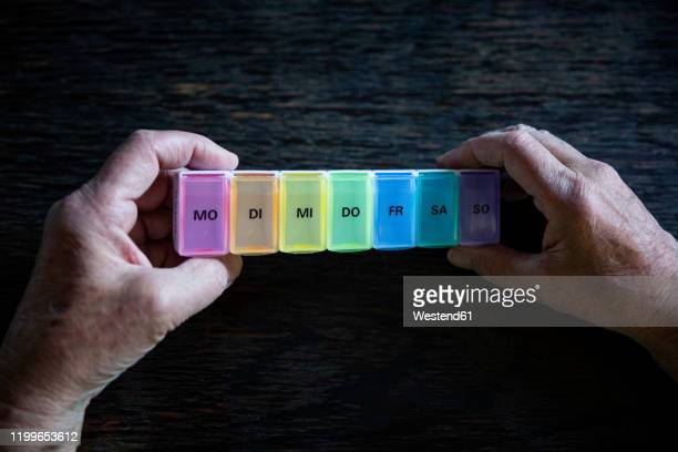 senior holding pill box - day of the week stock pictures, royalty-free photos & images