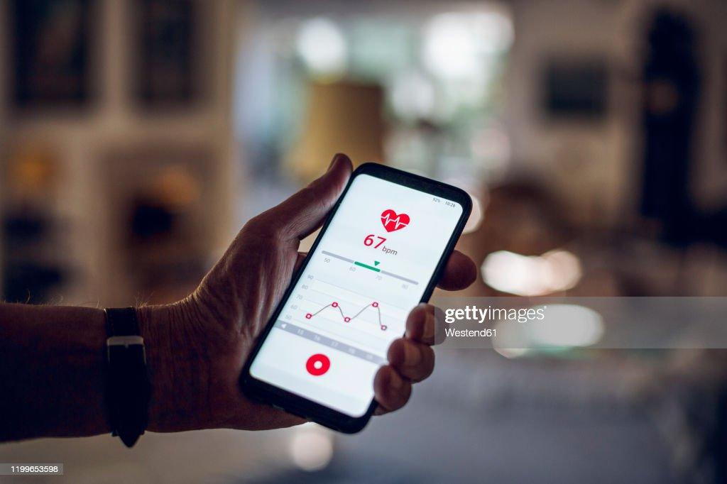 Senior holding smartphone, using fitness app : Stock Photo