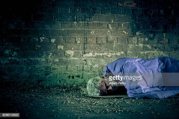Senior homeless caucasian male sleeping rough outdoors