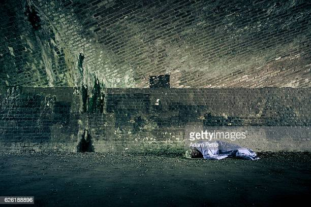 senior homeless caucasian male sleeping rough outdoors - homeless foto e immagini stock