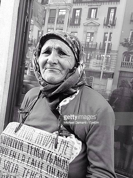 senior homeless woman with information sign against glass window in city - michael damanti fotografías e imágenes de stock