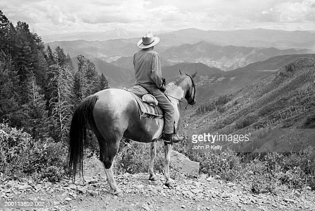 senior horseman on quarter horse looking at valley, rear view (b&w) - b fotos - fotografias e filmes do acervo