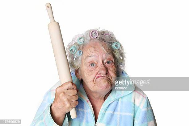 Senior Humor: cranky woman making faces and holding rolling pin