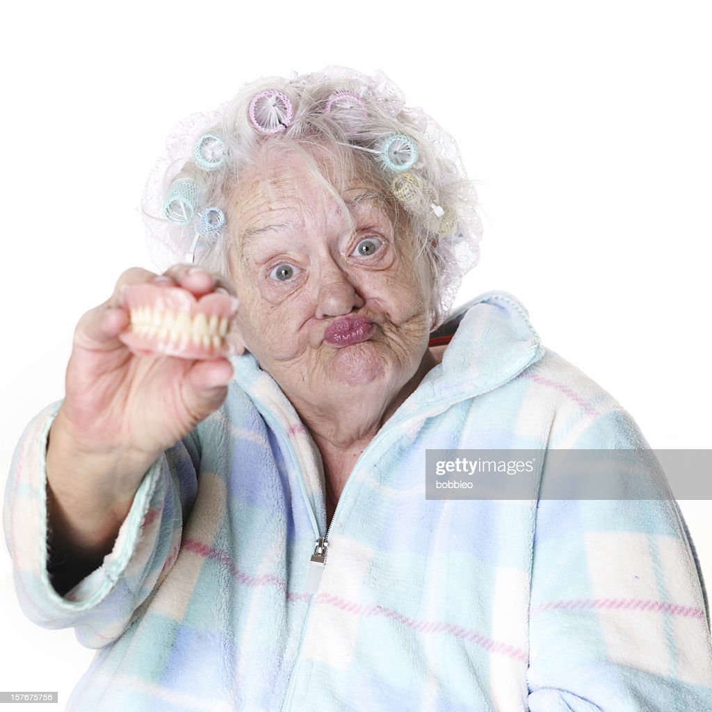 Senior Humor: woman holding false teeth : Stock Photo