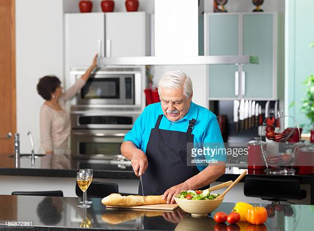 Senior husband and wife in the kitchen cooking