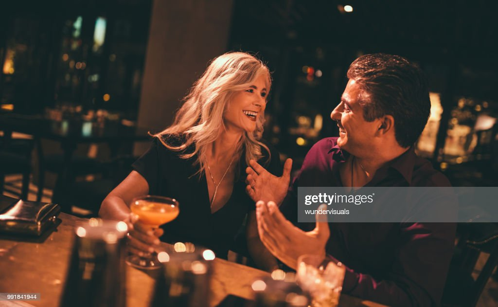 Senior husband and wife laughing and having drinks at bar : Stock Photo