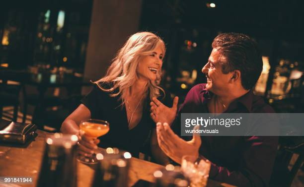 senior husband and wife laughing and having drinks at bar - flirtare foto e immagini stock