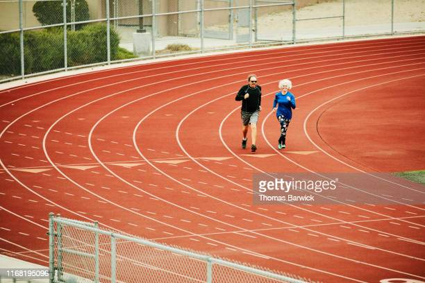 senior husband and wife running together on track - forward athlete stock pictures, royalty-free photos & images