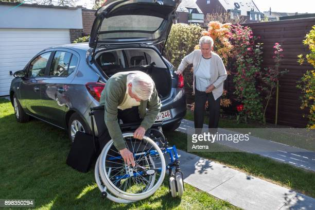 Senior husband assembling wheelchair from physically disabled elderly wife in front of car after returning at home