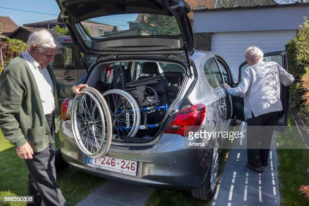 Senior husband fitting dismantled wheelchair from physically disabled elderly wife in car trunk at home before going for a ride