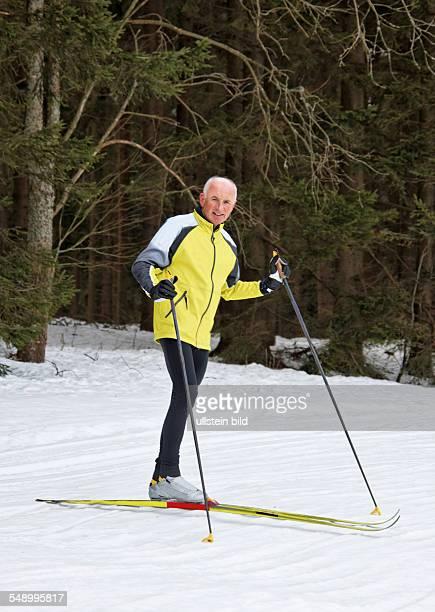 Senior im Winter auf Schnee beim Langlauf mit Skiern