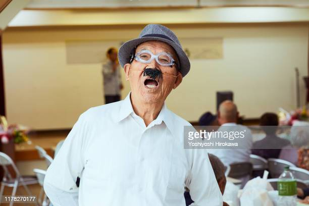 "senior in disguise waiting for the turn of ""helping hands"" comedy show - chairperson stock pictures, royalty-free photos & images"