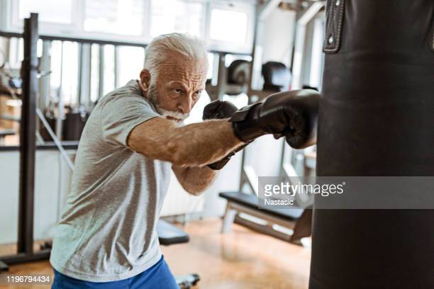 senior in gym training boxing - combat sport stock pictures, royalty-free photos & images