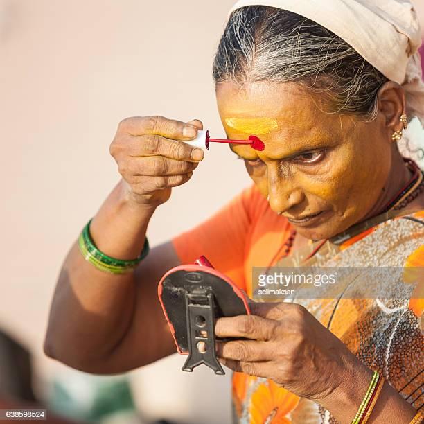 Senior Indian Woman Painting Bindi On Her Face