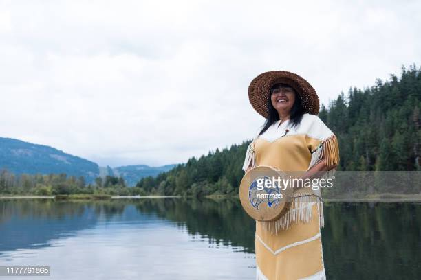 a senior indigenous canadian woman stands with her musical instrument - eskimo foto e immagini stock