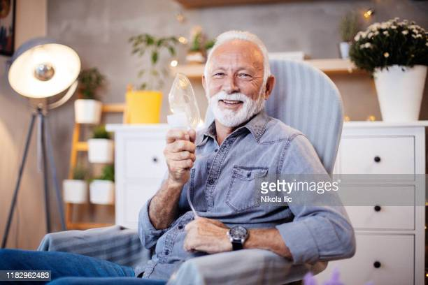 senior inhalation therapy in progres. - respiratory machine stock pictures, royalty-free photos & images
