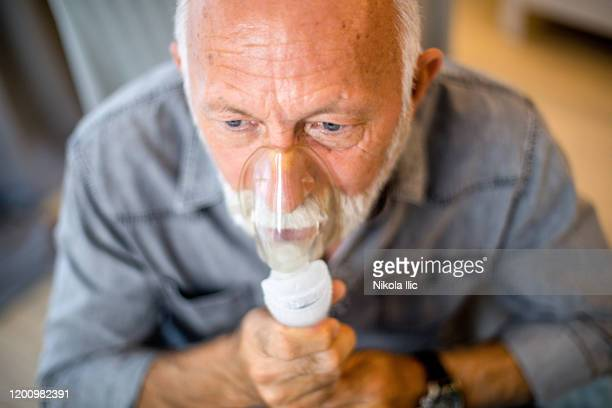 senior inhalation therapy in progres. - nose mask stock pictures, royalty-free photos & images