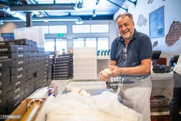 senior italian man working pizza dough - pizzeria stock pictures, royalty-free photos & images