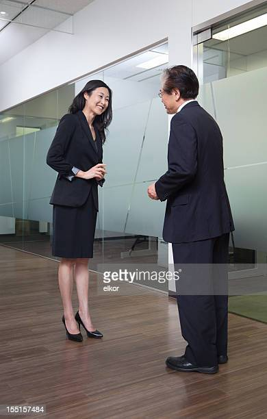 Senior Japanese businessman greats female boss with a gentle bow.