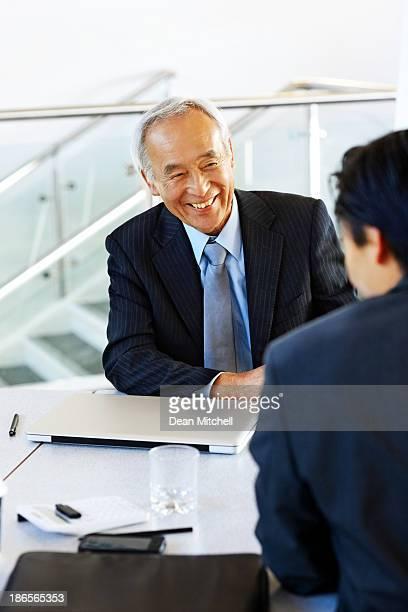 Senior japanischen Geschäftsmann, im Gespräch mit einer jungen Kollegen