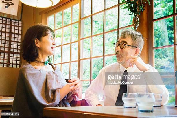 Senior Japanese couple laughing at cafe