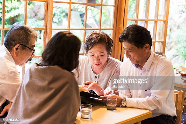 Senior Japanese Couples Look at Menu in Kyoto Restaurant Japan