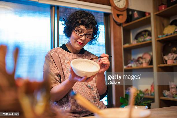 Senior Japanese Craftsperson painting a paper bowl