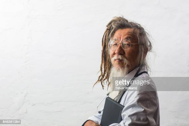 a senior japanese doctor with dreadlocks with a digital tablet - offbeat stock pictures, royalty-free photos & images