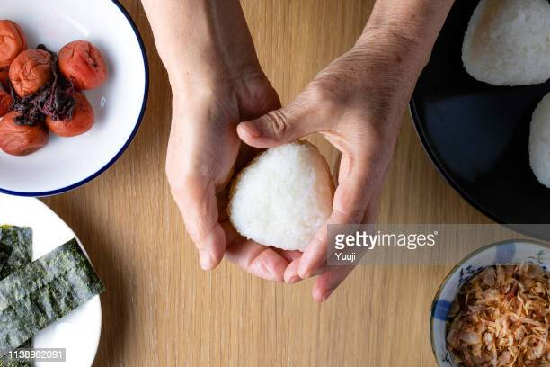 senior japanese female hand holding a rice ball. ingredients are umeboshi, dried bonito and nori. - rice ball stock pictures, royalty-free photos & images