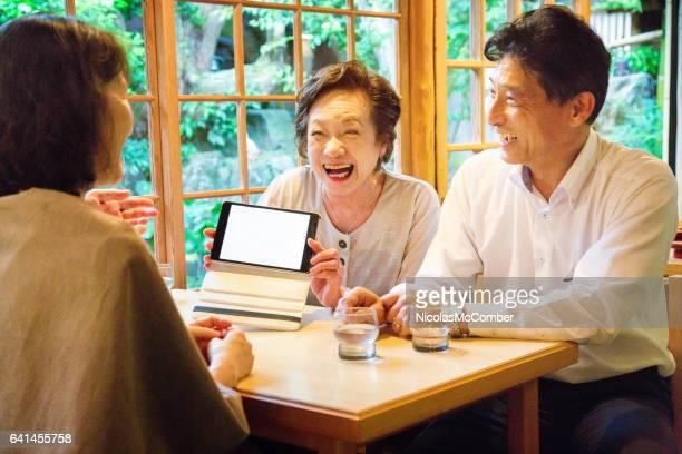シニア日本女性幸せを示しています空白タブレットのカフェで