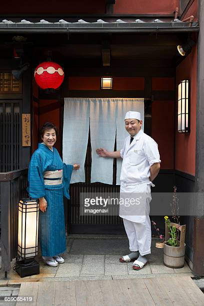 Senior Japanese hostess and cook smiling in front of Japanese restaurant