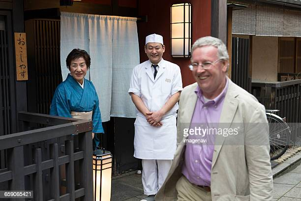 Senior Japanese hostess and cook watching after Caucasian customer
