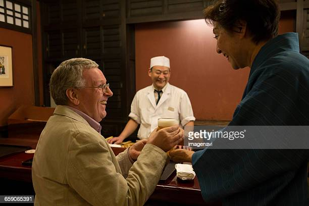 Senior Japanese hostess passing beer to mature Caucasian man