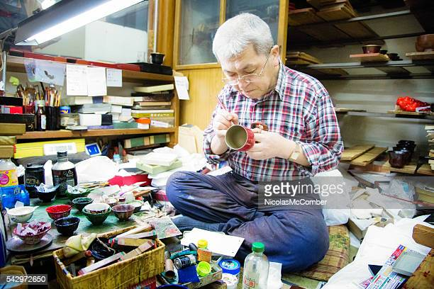 Senior Japanese male lacquer wood artisan painting a cup
