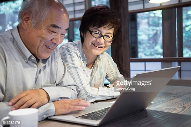 Senior Japanese man and mature woman using laptop
