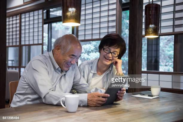 Senior Japanese man and mature woman using tablet