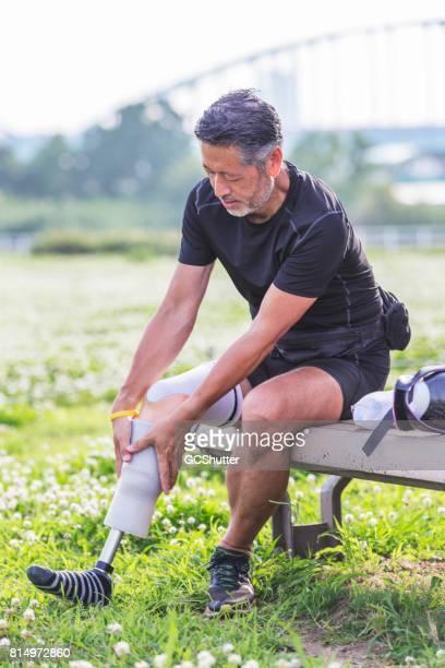 Senior Japanse man buigen meer dan als u wilt koppelen de sport prothetische ledematen