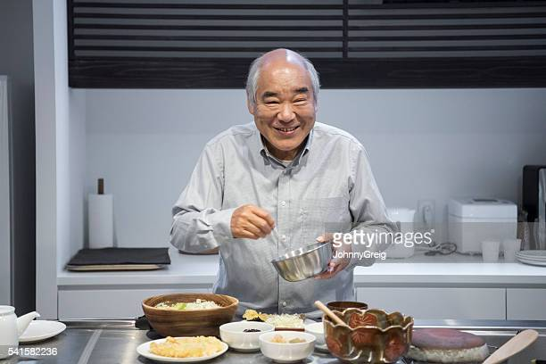 Senior Japanese man making dinner in kitchen, smiling