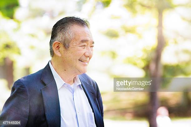 Senior Japanese man smiling in Yoyogi park looking away