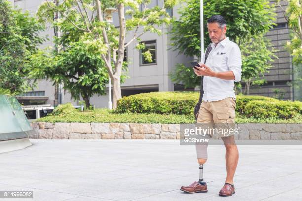 Senior Japans mens staande op een straat die reageren op een bericht op zijn smart phone