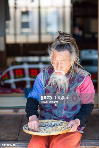 Senior Japanese man with dreadlocks sorting sun dried homegrown fruits and vegetables