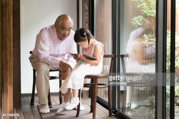 デジタル タブレットを使用しての孫娘と年配の日本人男性