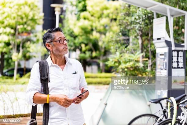 Senior Japanse man met zijn smartphone op zoek naar zijn bestemming