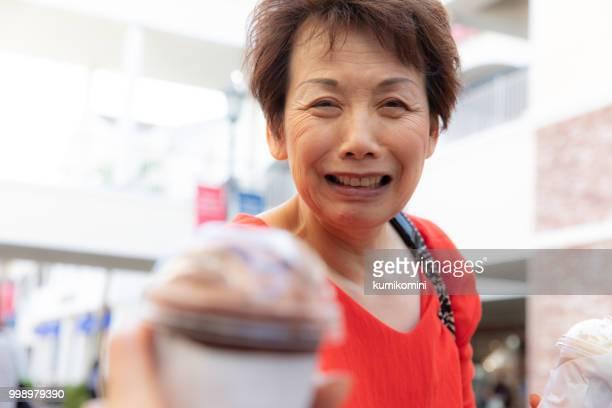 Senior Japanese woman bringing cold drink