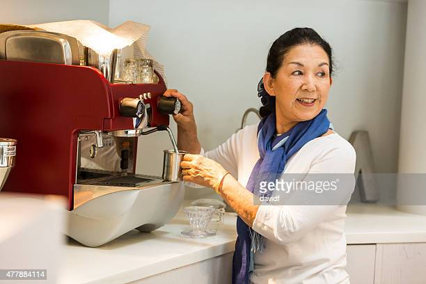 Senior Japanese Woman Making Coffee in a Cafe